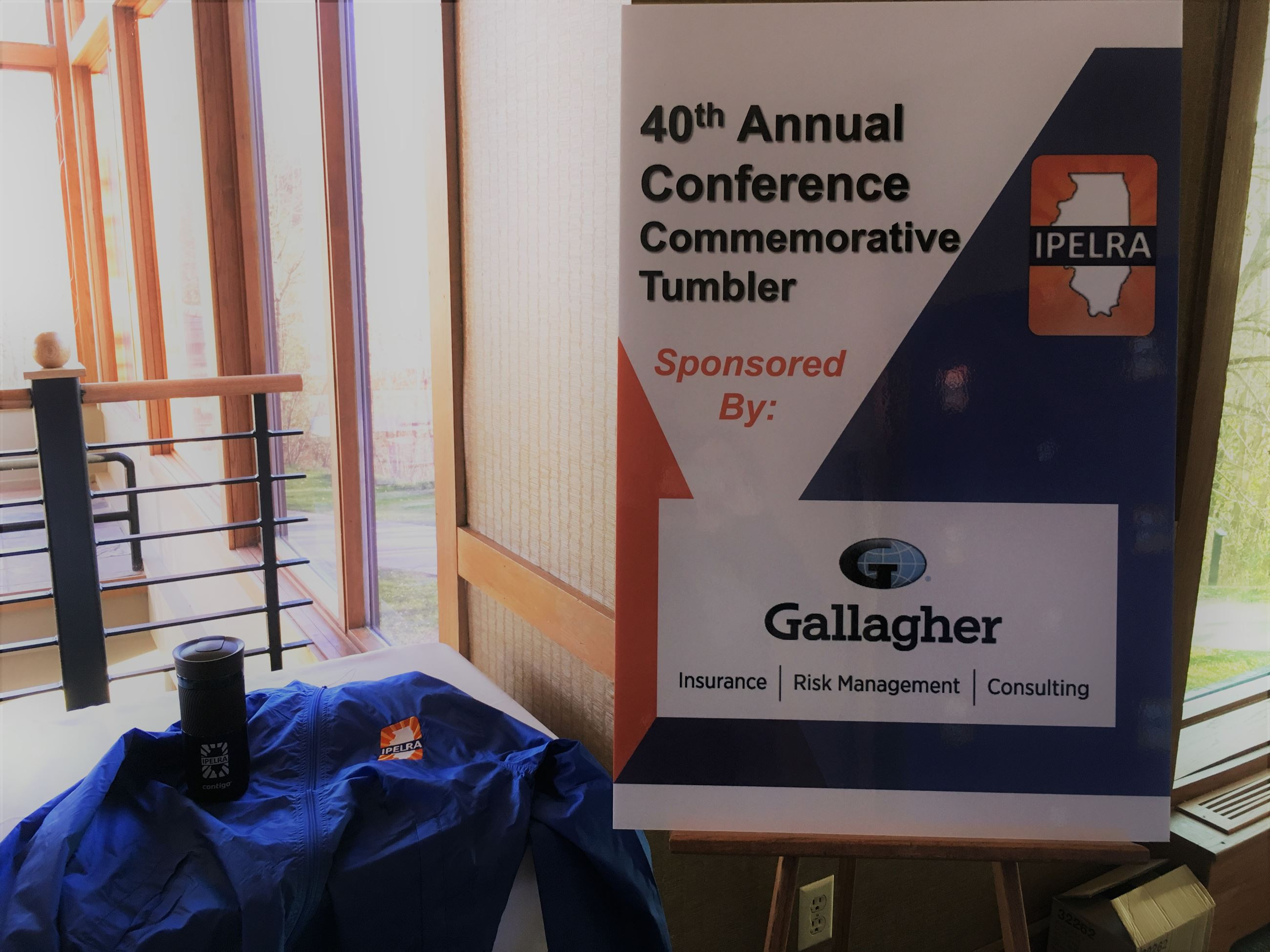 jacket, travel mug, and poster showing the sponsor Gallagher