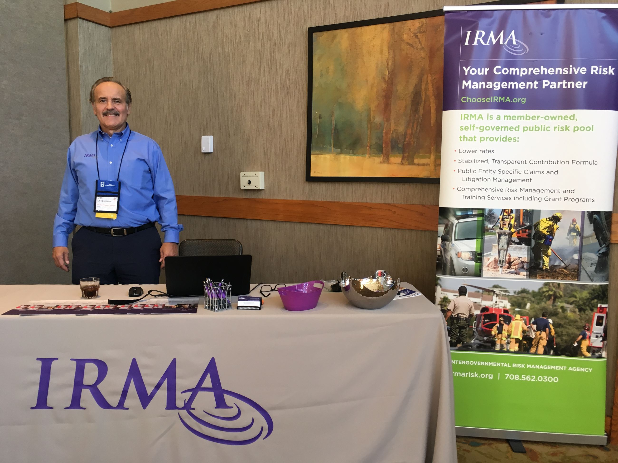 man standing at IRMA sponsor table