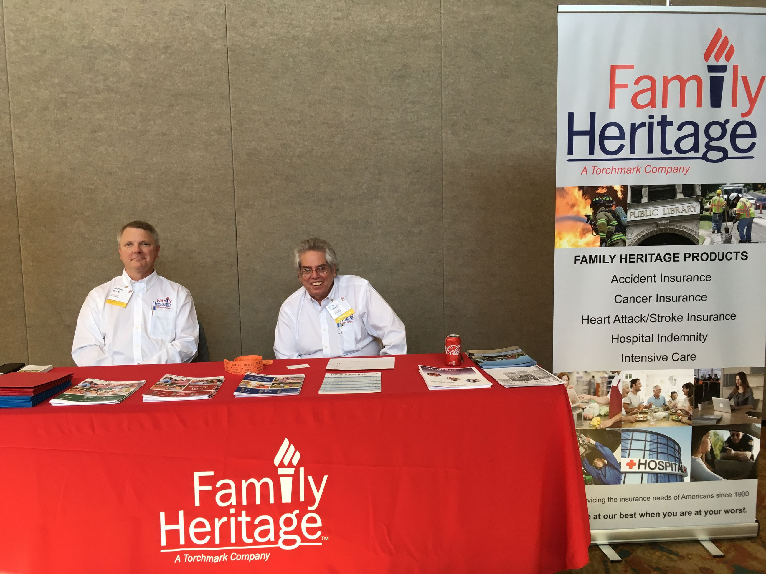 2 men sitting at Family Heritage sponsor table