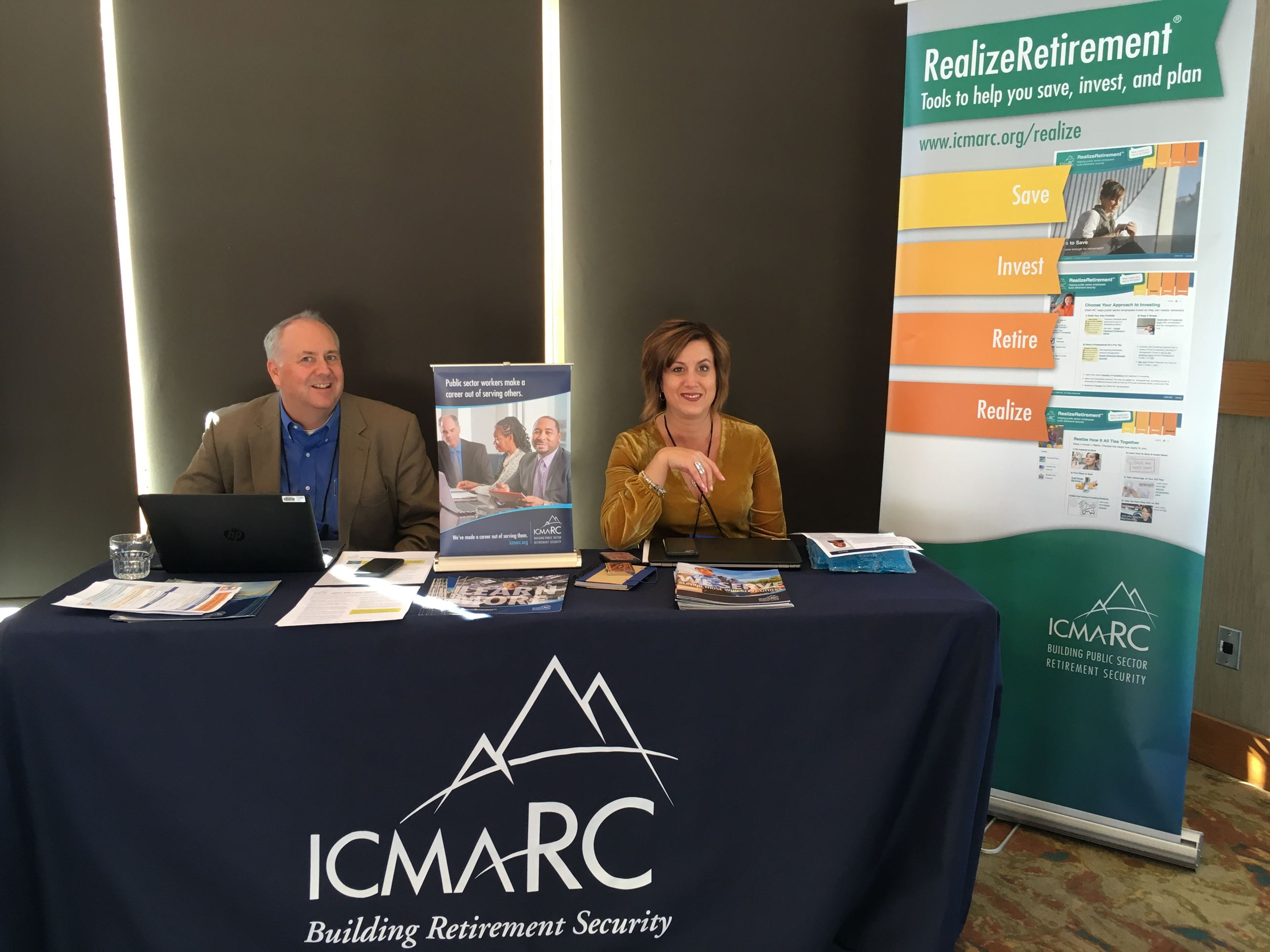 2 people sitting at table with ICMA-RC sponsor materials