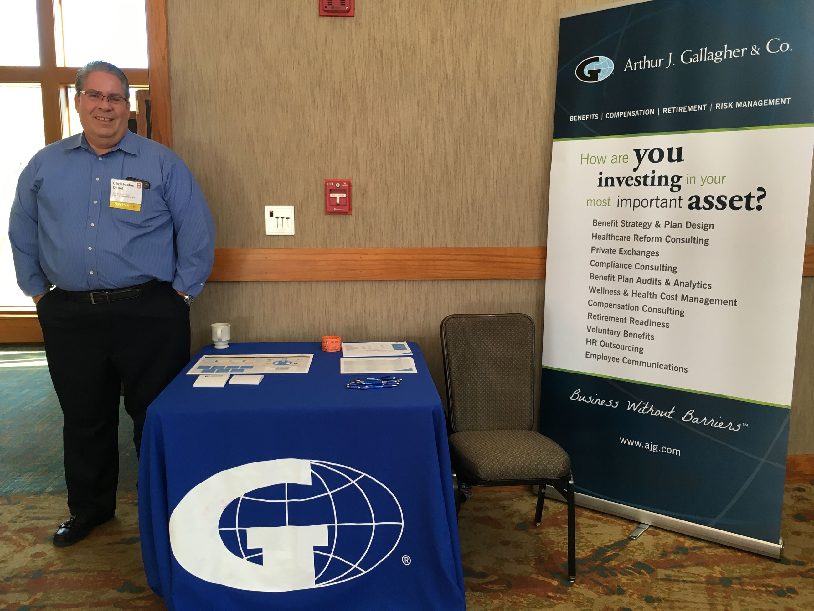 man standing next to table with Gallagher materials