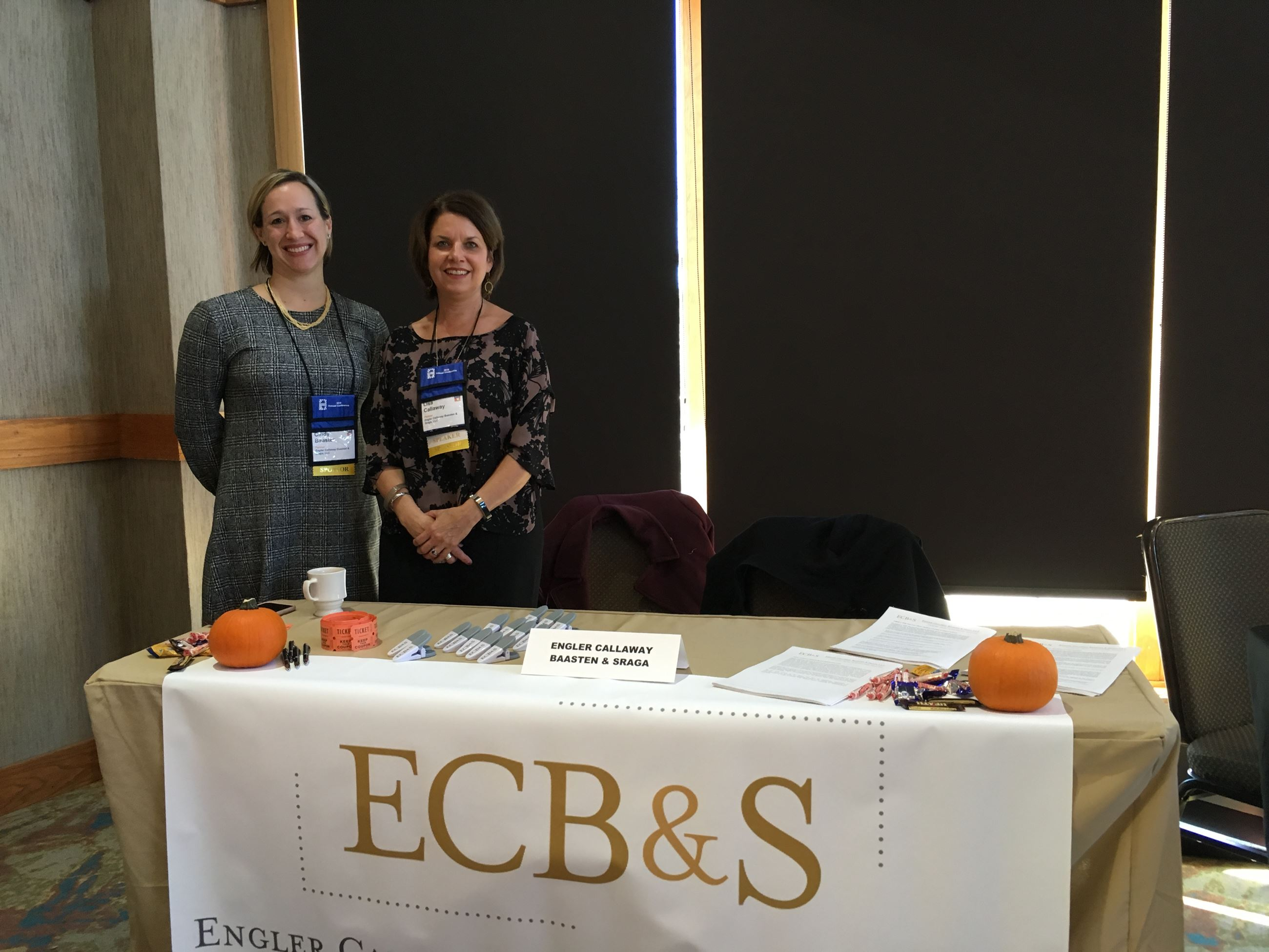 2 women standing next to a table with ECB&S materials