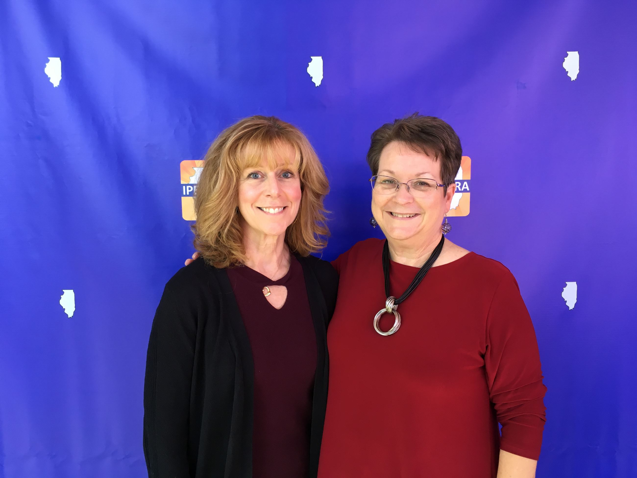 2 women standing next to each other in front of a blue background with IPELRA logos